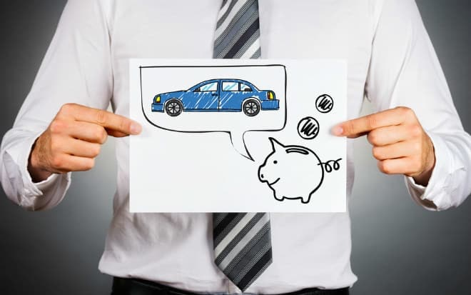 Man holding a paper with a piggy bank and car drawing