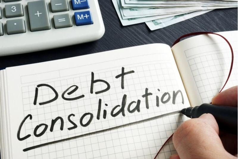 Debt cosolidation on maths paper alongside a calculator