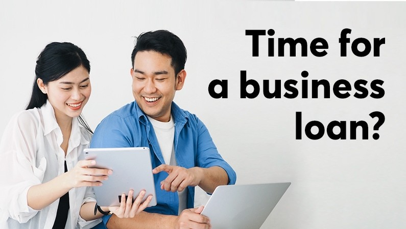 man and woman smiling holding papers illustrating business loan application
