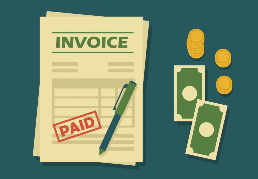 sample paid invoice form sitting beside loose money bills, coins and a pen
