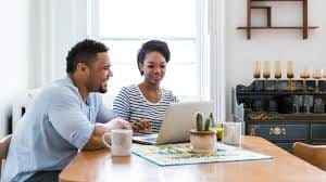 Smiling man with a coffee cup on the table sitting beside a smiling woman staring at a laptop