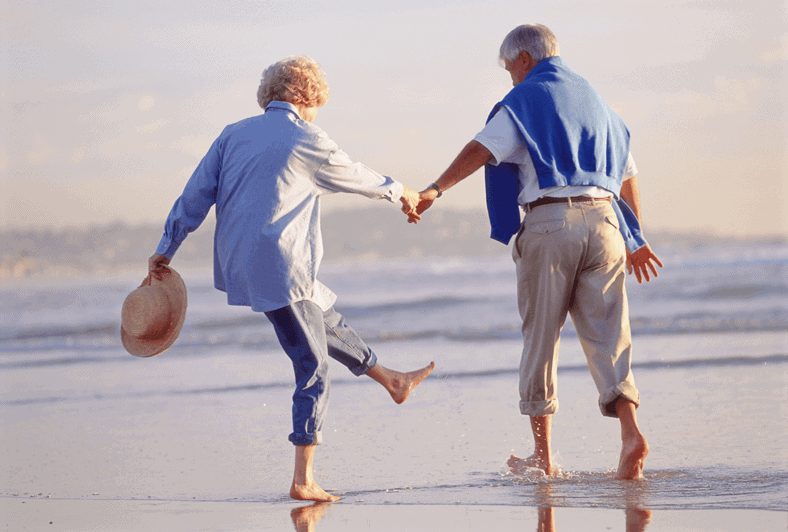 Older couple holding hands walking on the beach and splashing water