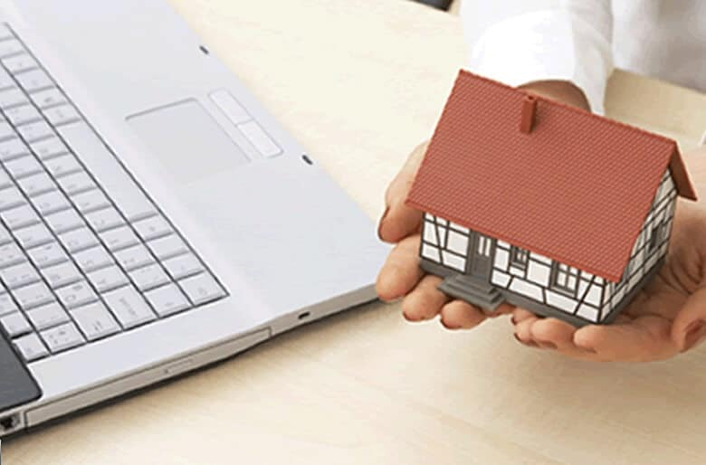 Hands holding a model house besides a laptop