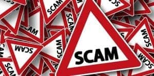 Pile of warning signs written scam