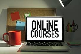 Laptop with ONLINE COURSES on display with red cup on one side and a cupful of pens on the other