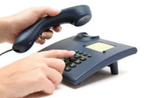 Two hands holding onto a landline phone