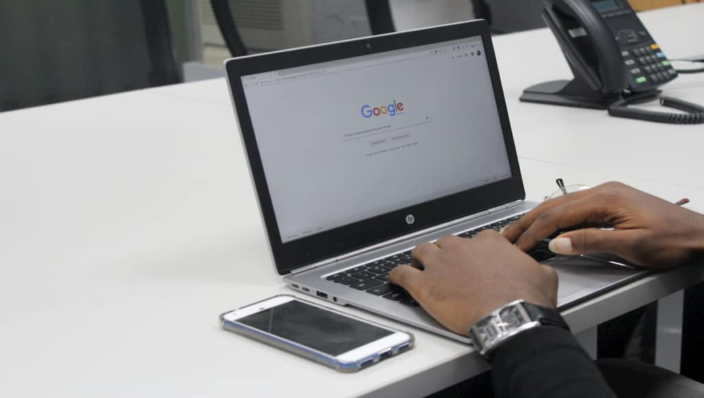 A man is using Google search on his laptop.
