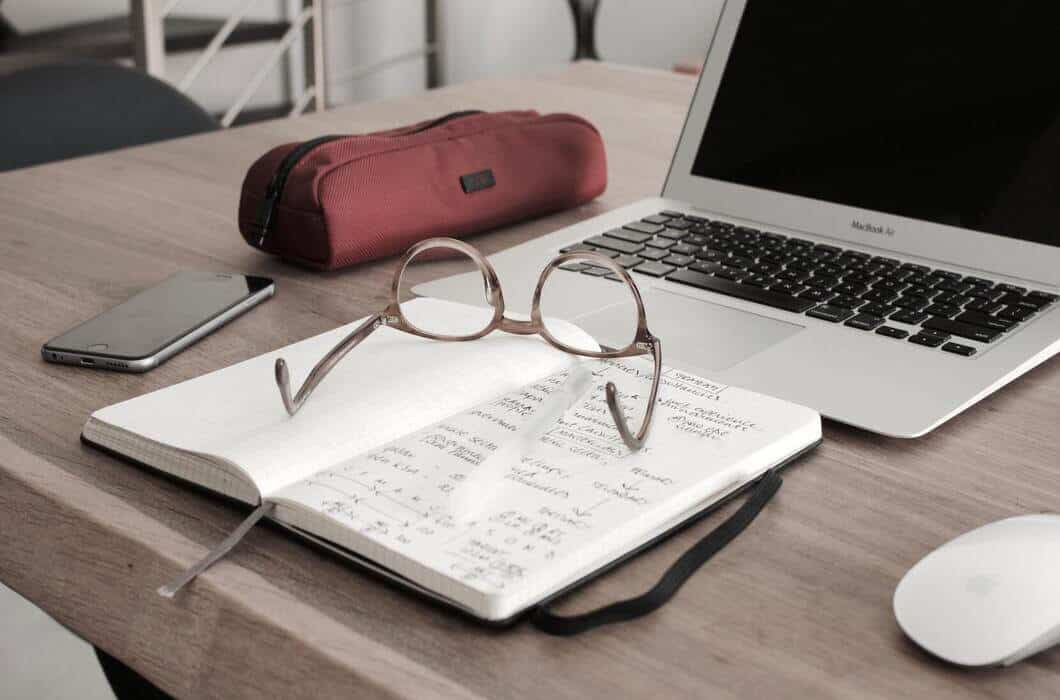 A pair of spectacles on a book next to a computer - investing in mutual funds- Photo by Didier Weemaels on Unsplash